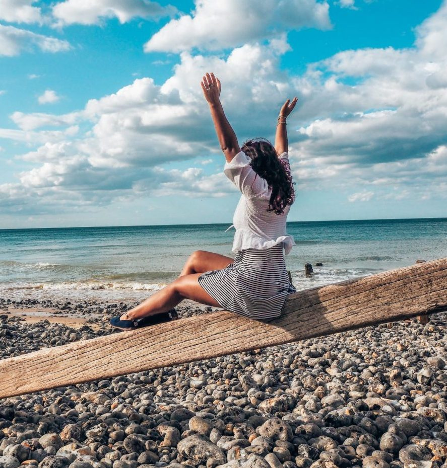 uk road trips – girl on wooden beam by ocean, shingle beach, norfolk. hands in air,