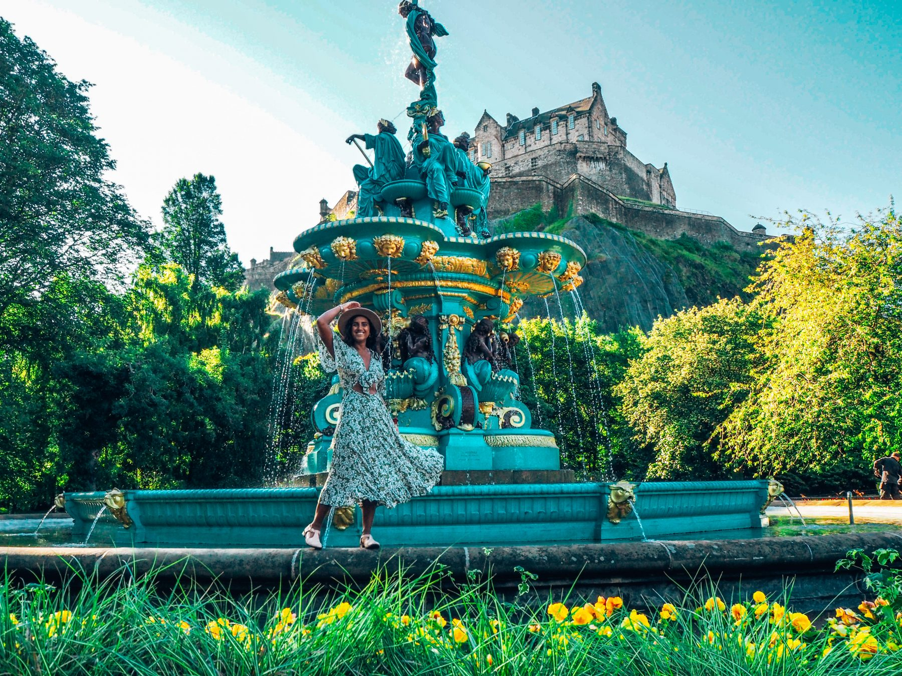 Scotland road trip, Lucy stands on Edinburgh fountain with view of Edinburgh castle